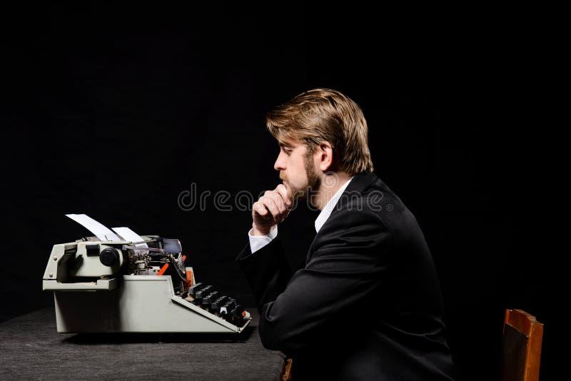 Pisarz, mężczyzna pisać na maszynie na maszyna do pisania w czarnej kurtce zdjęcia royalty free
