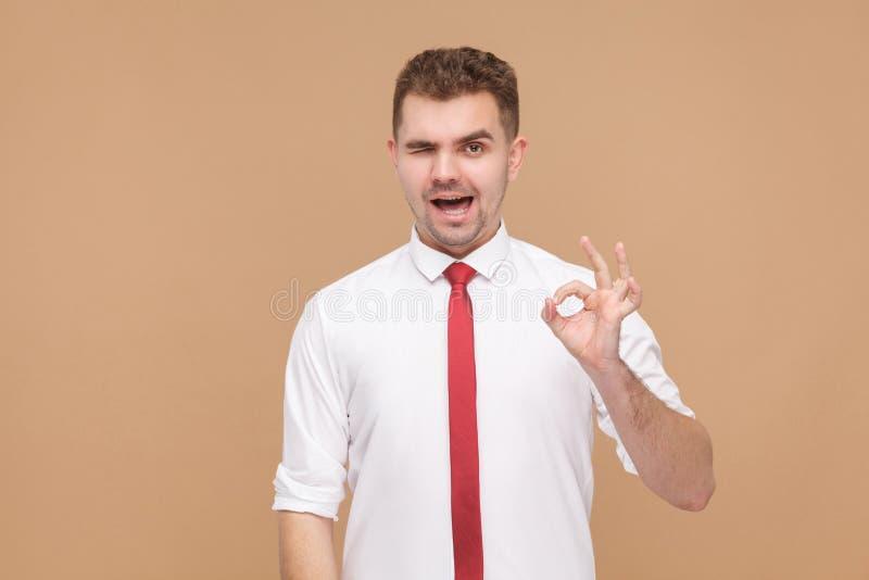 Piscadela atrativa do homem de negócios, sorrindo e mostrando o sinal aprovado imagens de stock