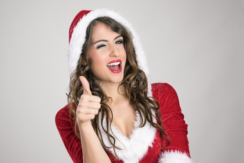 Piscadela fêmea encapuçado de sorriso de Santa com o polegar acima do gesto de mão da aprovação foto de stock royalty free