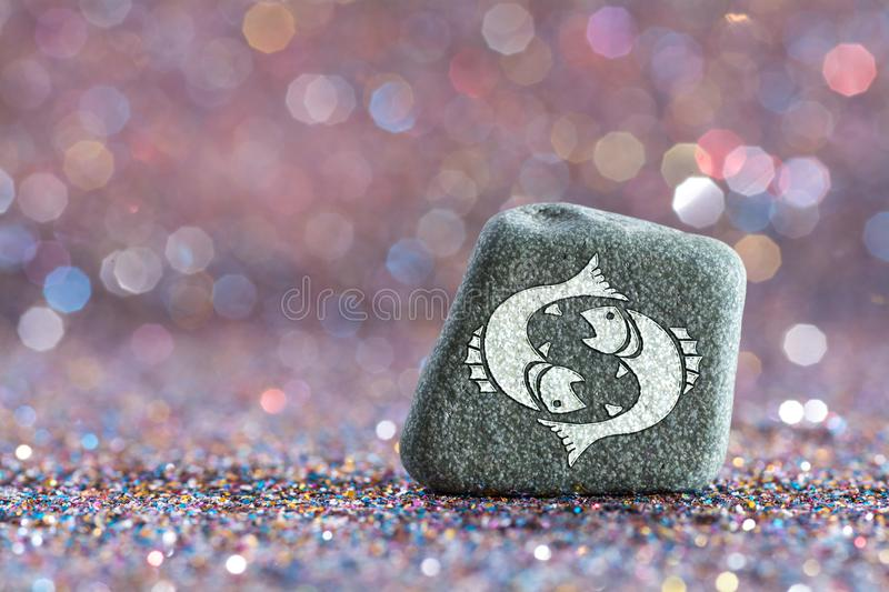 Pisces zodiac sign. A green stone with Pisces zodiac sign on glitter boke light background stock image