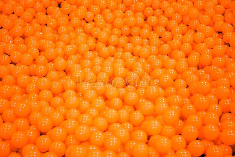 Piscina anaranjada de la bola Muchas bolas anaranjadas en la caja Actividad juguetona para los niños foto de archivo