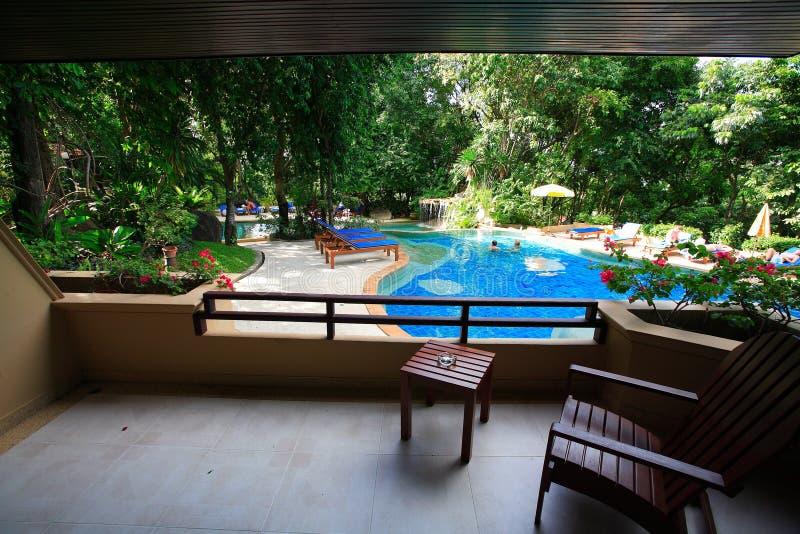 Piscina, chaise-lounge del sole accanto al giardino e costruzioni fotografie stock libere da diritti