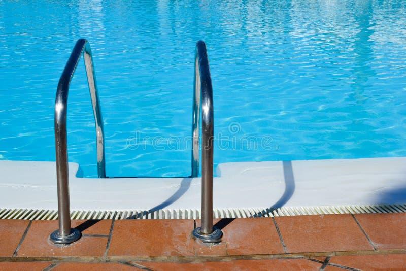 Piscina con el fondo de la escalera de las barras de gancho agarrador Concepto del verano imagen de archivo
