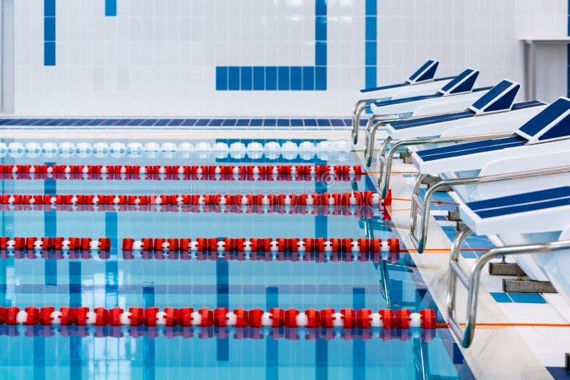 Piscina con i vicoli rossi e bianchi contrassegnati Piscina vuota senza gente con acqua stagnante calma fotografia stock