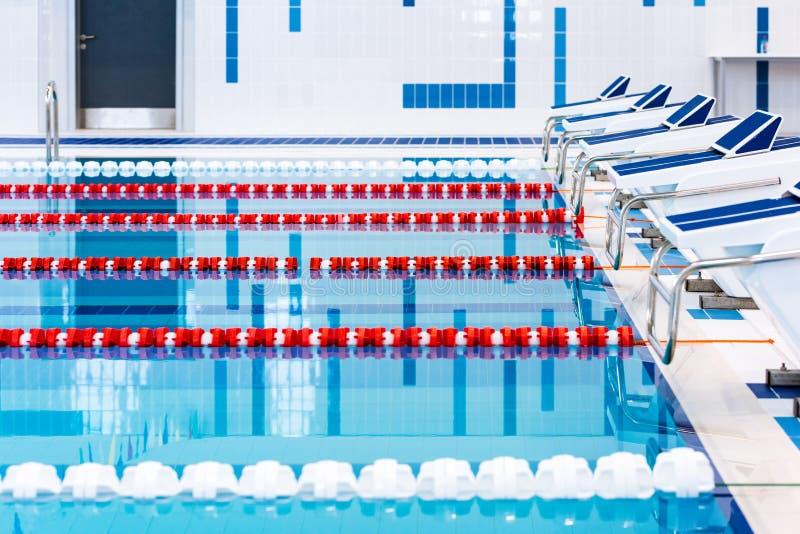Piscina con i vicoli rossi e bianchi contrassegnati Piscina vuota senza gente con acqua stagnante calma fotografie stock