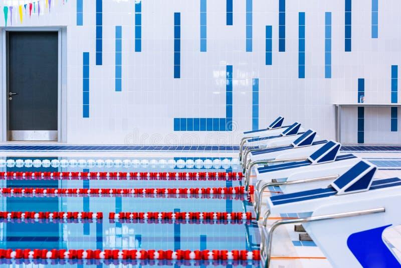 Piscina con i vicoli rossi e bianchi contrassegnati Piscina vuota senza gente con acqua stagnante calma immagine stock
