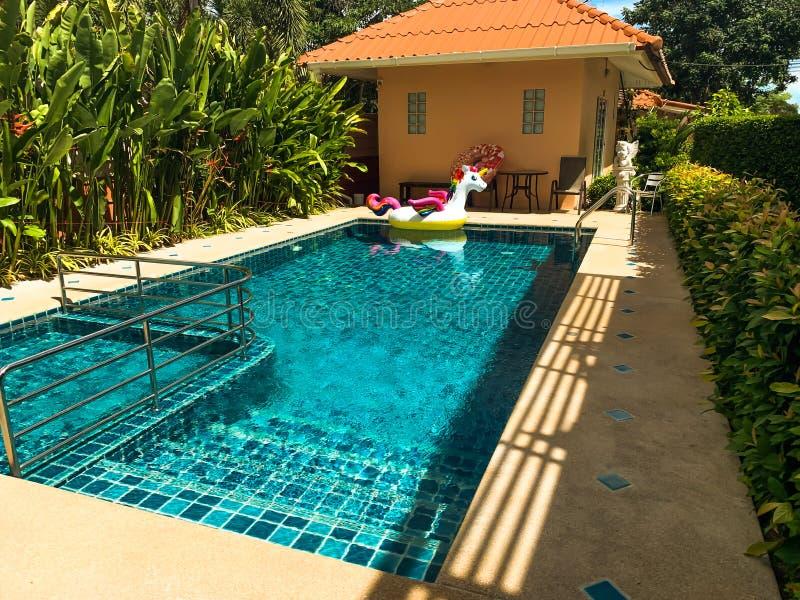 A piscina da água azul com as telhas de assoalho sob árvores verdes fecha-se acima com um jardim foto de stock