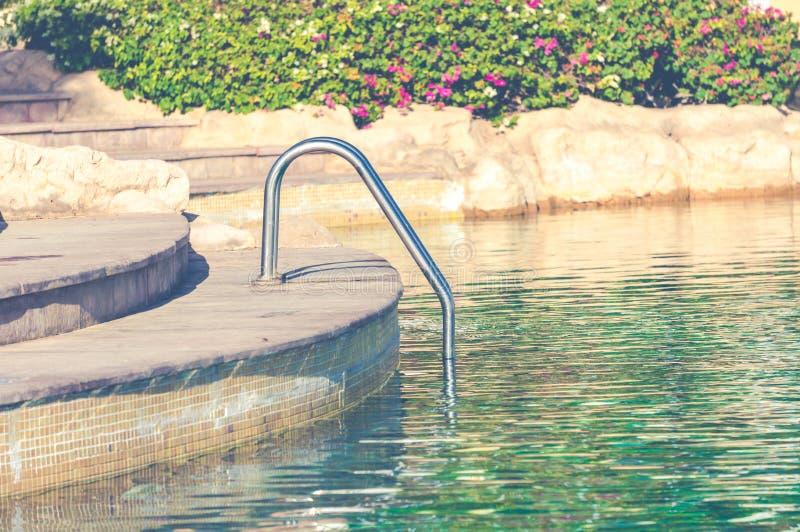 Piscina de Swimmimg con las barras de gancho agarrador de la escalera de la piscina fotografía de archivo libre de regalías