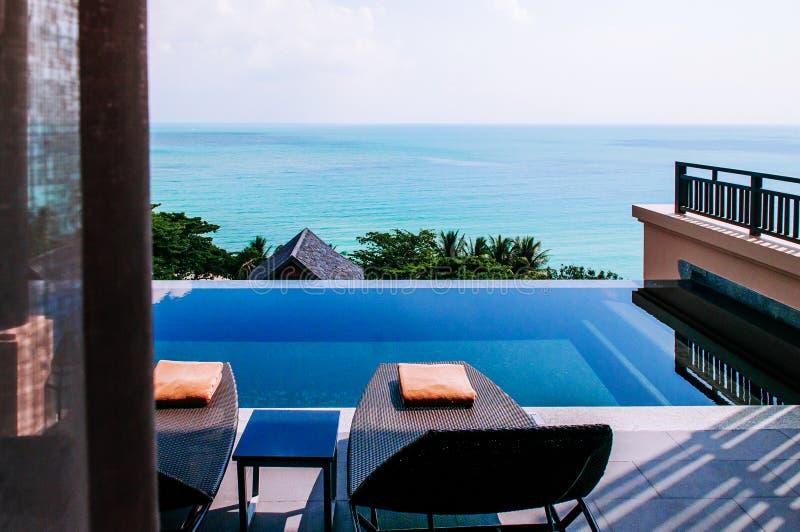 Piscina del borde del infinito con el chalet tropical del centro turístico del seaview con la cama de la piscina fotos de archivo libres de regalías