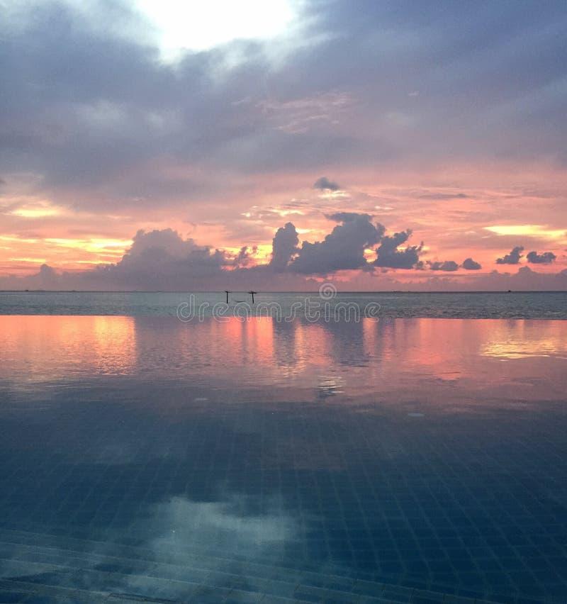 Piscina del infinito en la playa en la puesta del sol foto de archivo libre de regalías