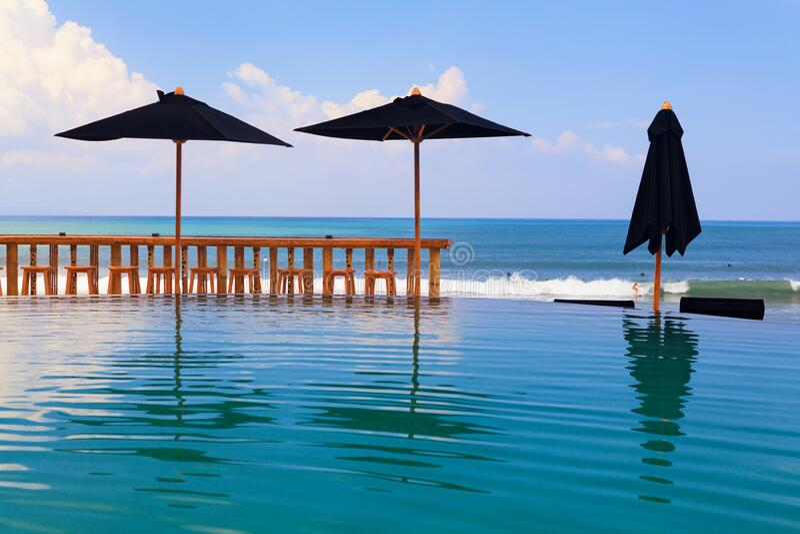 Piscina desbordante con bar de playa, sombrillas y salones fotos de archivo