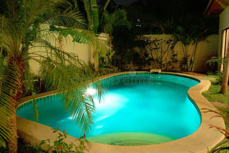Piscina di notte in giardino tropicale fotografia stock