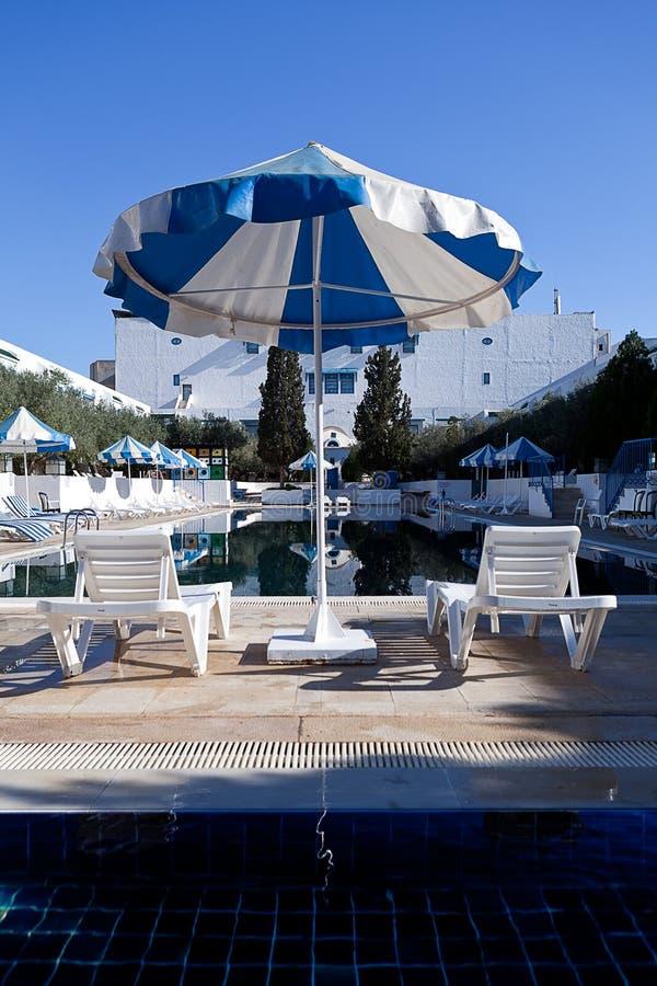 Piscina do hotel com os dois guarda-chuvas dos sunbeds imagens de stock royalty free