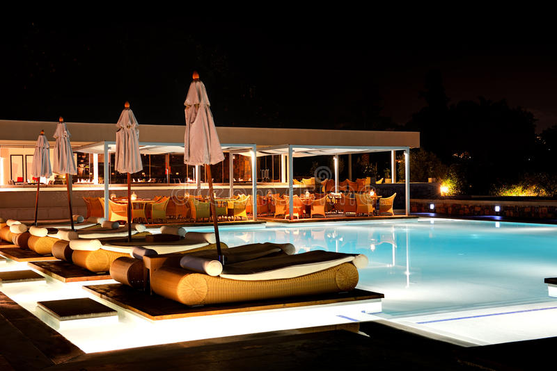 Piscina e barra nell'illuminazione di notte all'albergo di lusso fotografia stock