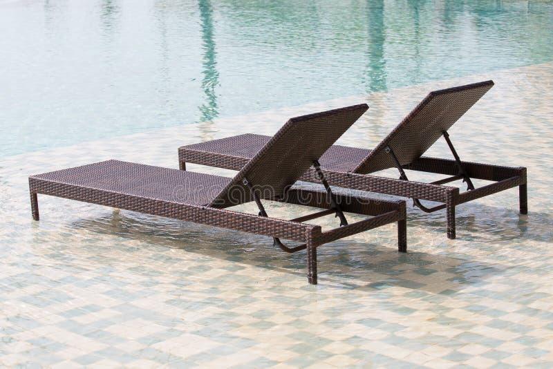 Piscina e duas cadeiras de plataforma, fim acima imagem de stock