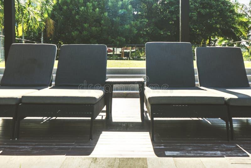 Piscina e tramonto laterali delle sedie di spiaggia fotografia stock libera da diritti