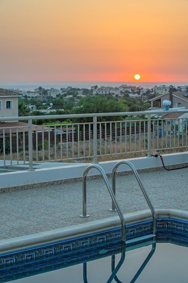 Piscina e tramonto sopra il mare sull'orizzonte immagine stock