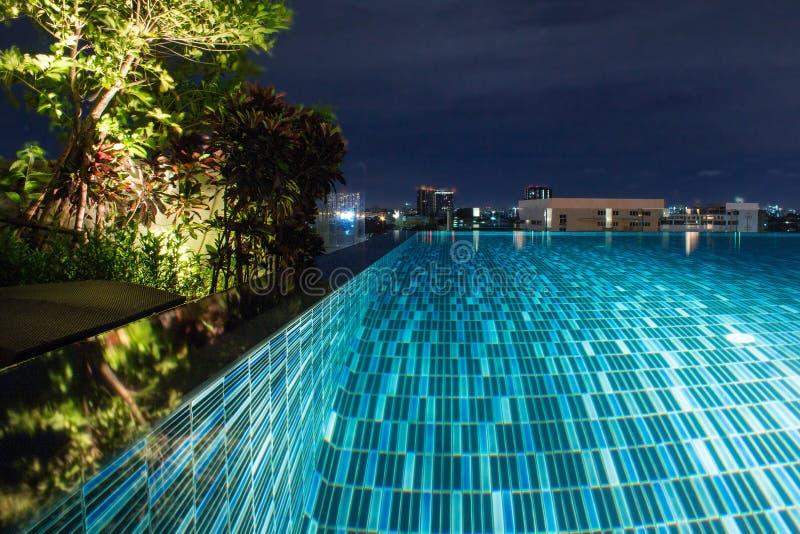 Piscina en la noche con verdor enorme y la iluminación para el diseño casero foto de archivo libre de regalías