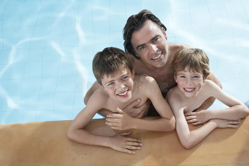 Piscina feliz de With Sons In del padre foto de archivo libre de regalías