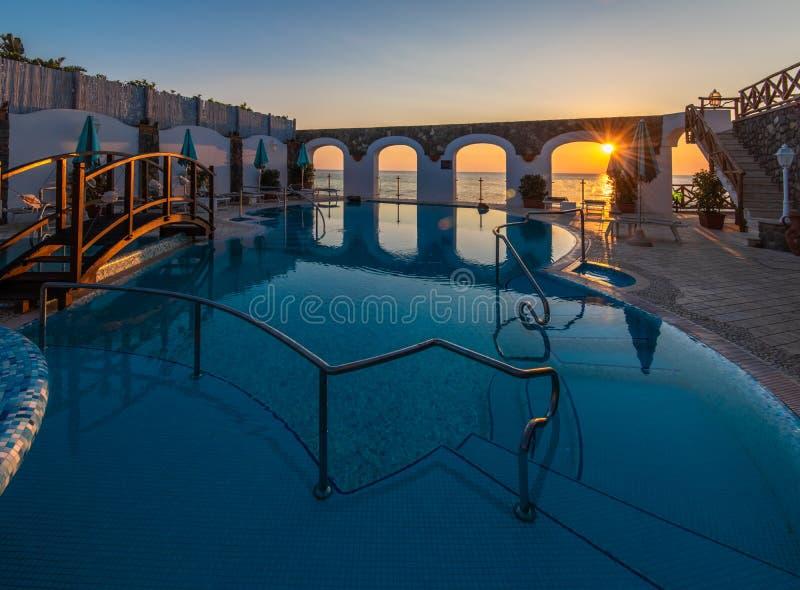 Piscina hermosa con el watere termal en la puesta del sol imagenes de archivo