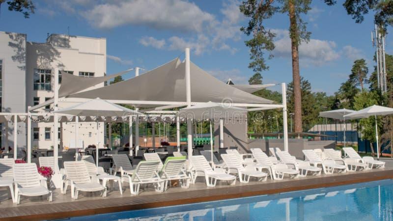 Piscina hermosa del verano con sunbed y parasoles en un centro de ocio del país Concepto de reconstrucción y de ocio imagen de archivo