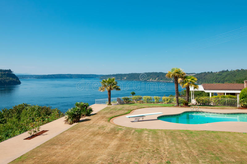 Piscina a la casa de lujo de la costa con el área y la visión grandes o de la hierba imagen de archivo