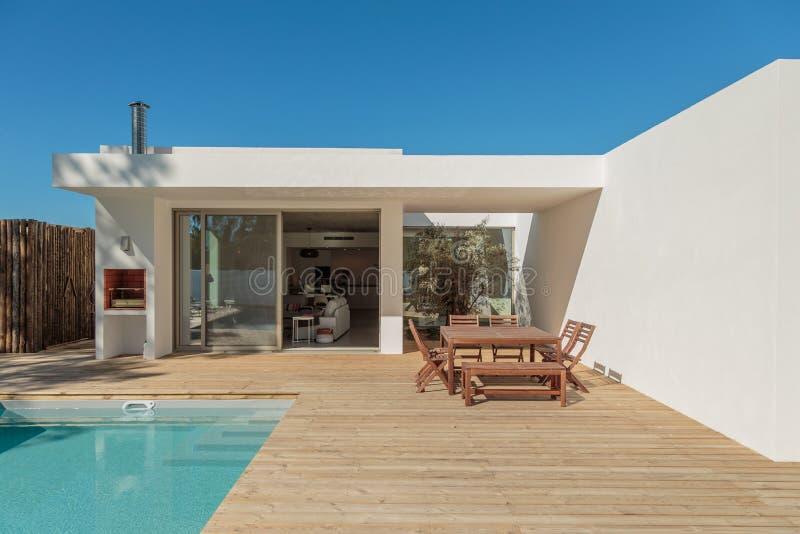 Piscina moderna del giardino della casa e piattaforma di legno fotografia stock