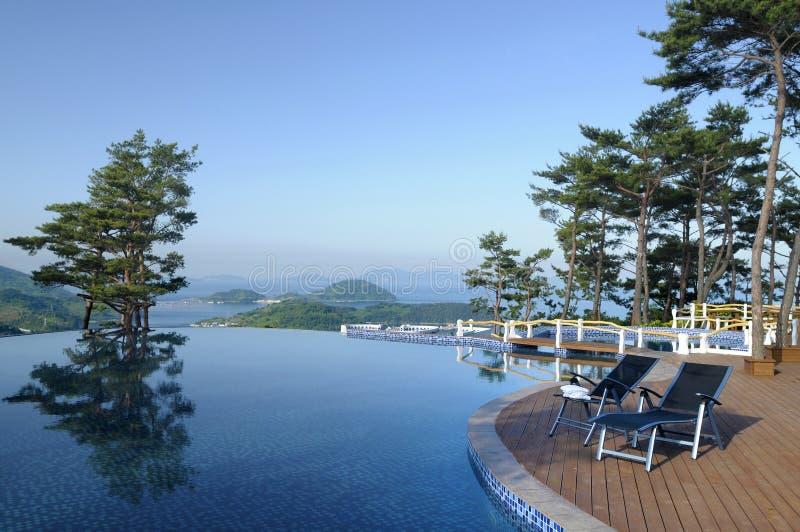 Piscina, montañas e islas del infinito del hotel de balneario en distancia foto de archivo