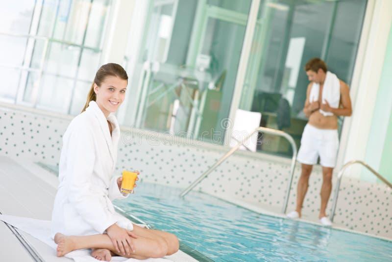 Piscina - a mulher nova relaxa no poolside imagens de stock