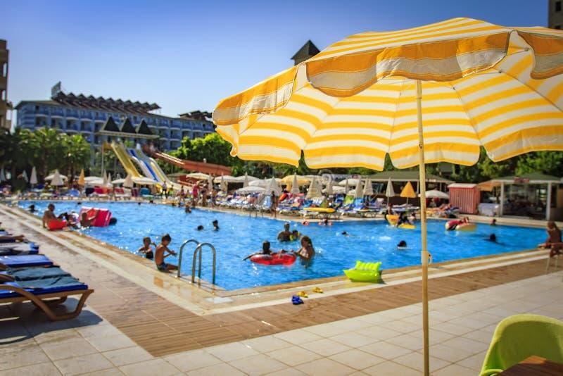 Piscina na estância tropical Guarda-chuva amarelo no fundo borrado de banhar turistas na associação no dia ensolarado brilhante fotografia de stock
