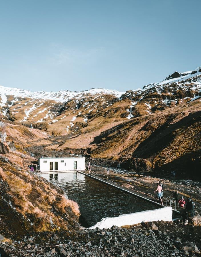 Piscina natural Seljavallalaug em Islândia com o homem na água e tempo nevado e montanhas toda ao redor ensolarado imagens de stock