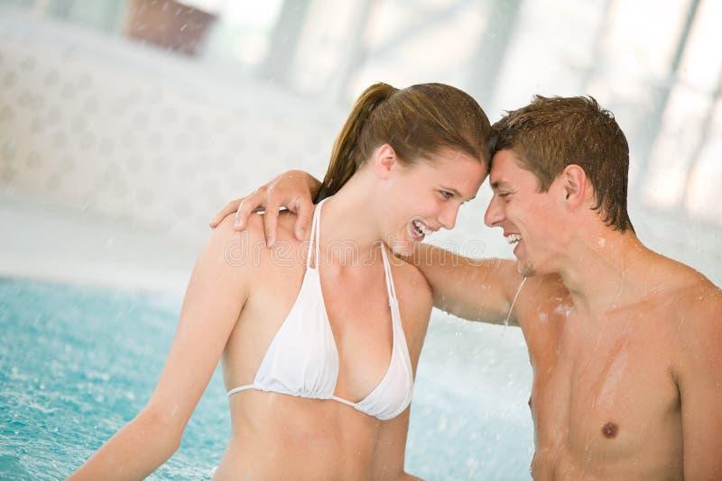 Piscina - os pares loving novos têm o divertimento foto de stock royalty free