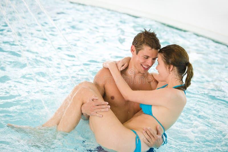 Piscina - os pares loving novos têm o divertimento fotografia de stock royalty free