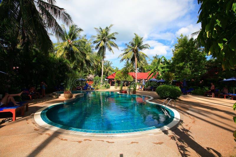 Piscina rotonda, chaise-lounge del sole accanto al giardino e bungalow immagine stock