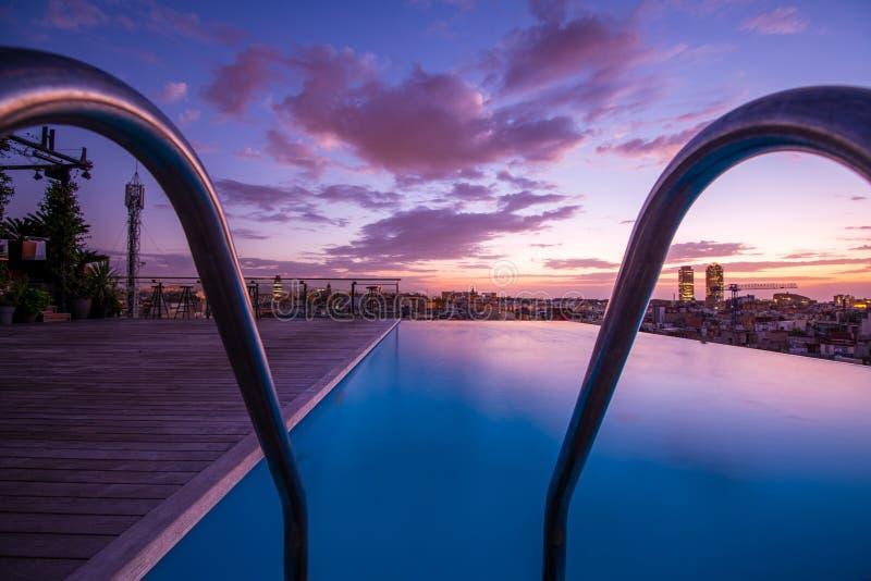 Piscina superior do telhado luxuoso com borda da infinidade, amanhecer, céu colorido fotos de stock