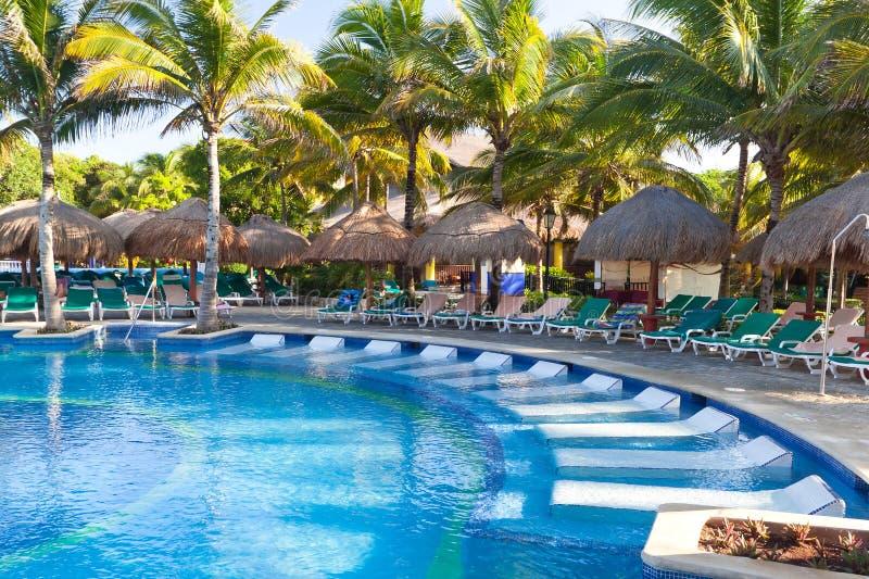Piscina Tropical Con Los Sunbeds Fotografía de archivo libre de regalías