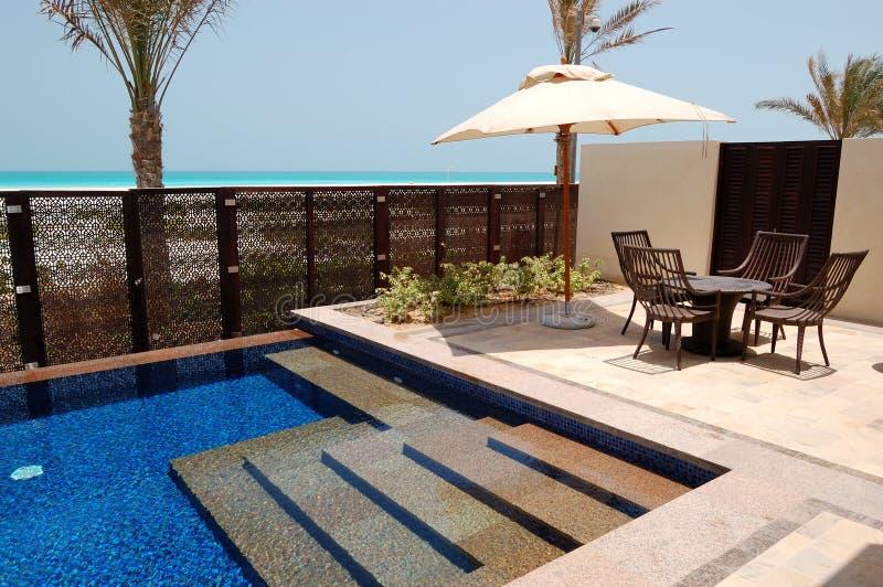 Piscina vicino alla spiaggia dell'albergo di lusso fotografia stock libera da diritti