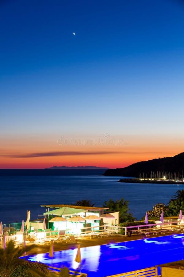 Piscina y barra por el mar en la puesta del sol en verano en Italia fotos de archivo