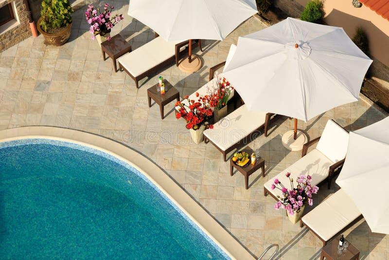 Piscina y salones con los parasoles foto de archivo libre de regalías