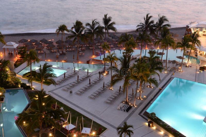 Piscinas del hotel en la puesta del sol fotografía de archivo