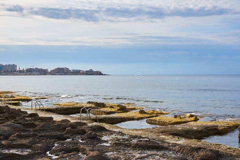 Piscinas rocosas por el mar con tres escaleras de la piscina imagenes de archivo