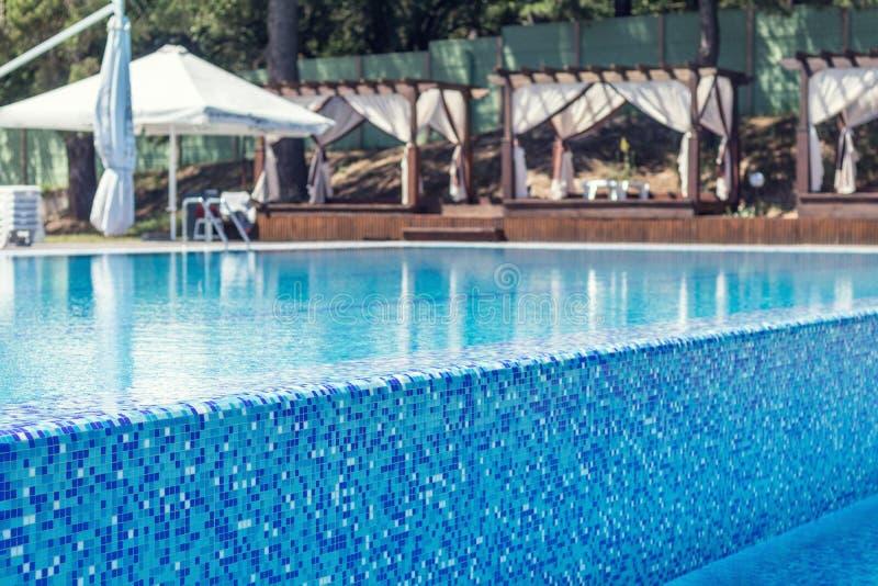 Piscine bleue avec la plate-forme en bois à l'hôtel image stock