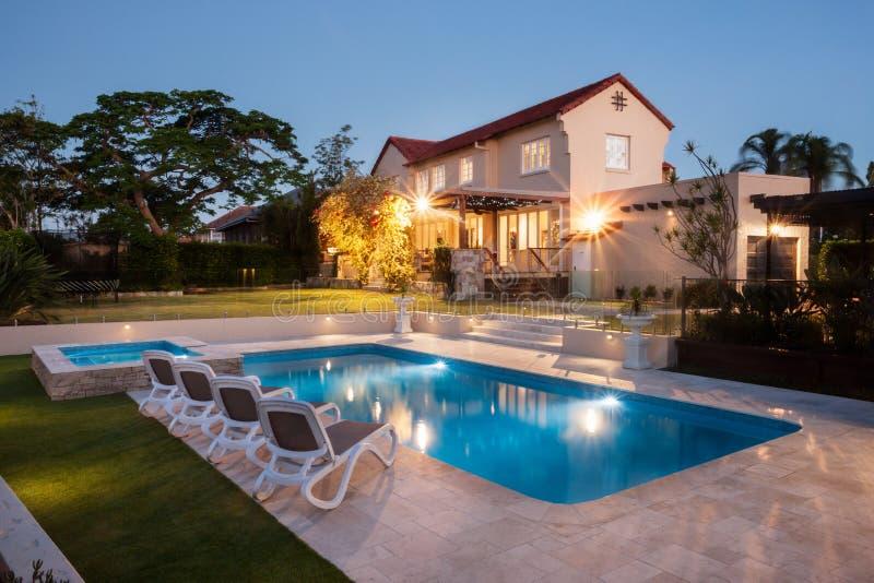 Piscine moderne avec une grande maison illuminée avec des lumières photos stock