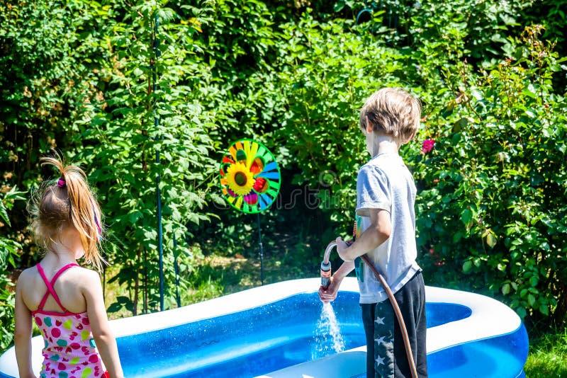 Piscine remplissante de petit garçon et de fille avec de l'eau photos libres de droits