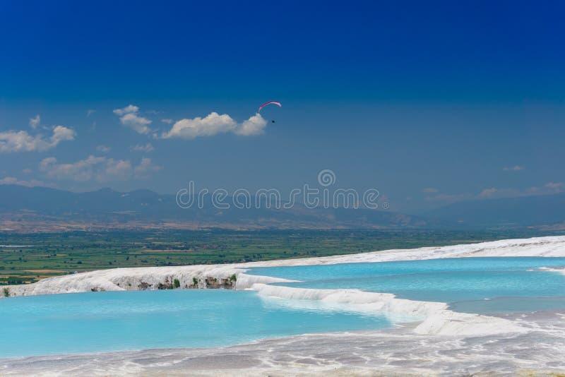 Piscines et terrasses bleues de travertin dans Pamukkale, Denizli, Turquie Ch?teau de coton Parapentisme dans le ciel photo stock