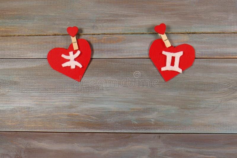 Piscis y gemelos muestras del zodiaco y del corazón Backgrou de madera imagen de archivo