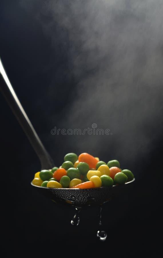 Piselli, mais e carota bolliti in una siviera con vapore immagine stock