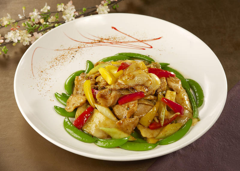 Piselli sauteed con il pollo ed il peperoncino rosso sul piatto bianco nel resto immagini stock libere da diritti
