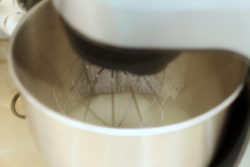 Piska ?ggvitor i yrkesm?ssig k?kblandare i en restaurang Närbilden piskade viter och socker i en planetarisk blandare för metall royaltyfri fotografi