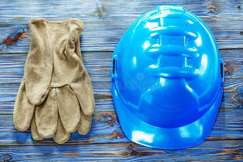 Piska skyddande handskar som bygger hjälmen på tappningträgalt arkivfoto